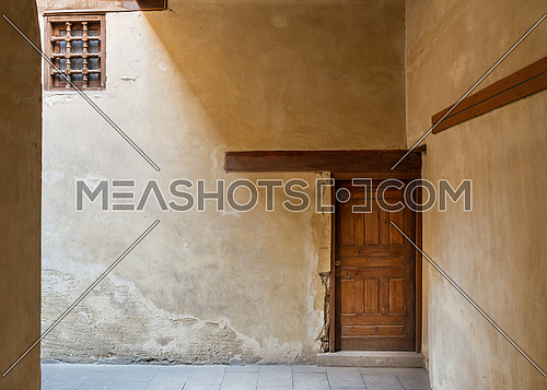 Wooden aged decorated door and small window covered with wooden grid on grunge stone wall and wood timber ceiling