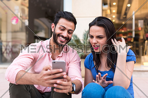 young couple sitting in the street using mobile phone in korba area at day