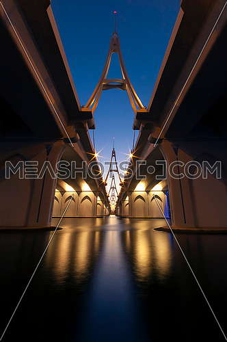 A low angle shot of Business Bay Bridge at the blue hour sky with under lights in Dubai , United Arab Emirates