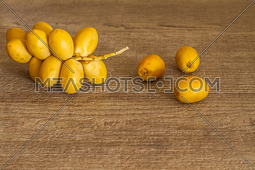 Yellow dates arranged on a wooden table