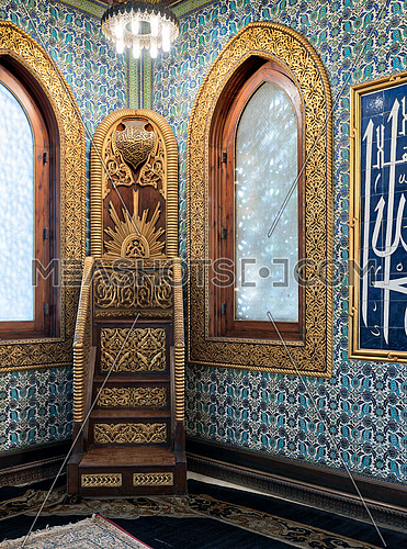 Wooden golden ornate minbar (Platform) and wooden arched window framed by golden ornate floral pattern over ceramic tiles wall with floral blue patterns at the public mosque of Manial Palace of Prince Mohammed Ali, Cairo, Egypt