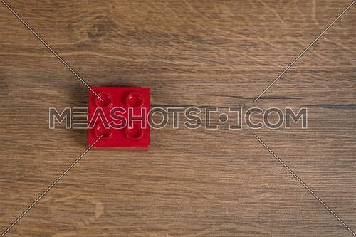 Top view on one square red toy brick on a brown wooden background. Toys in the table