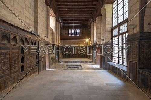 Hall at ottoman era historic house of Moustafa Gaafar Al Seleehdar located at Al Darb Al Asfar, Cairo, Egypt with decorated wooden ceiling, marble decorated floor and wooden ornate embedded cabinet