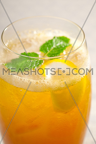 refreshing Ice tea closeup macro with lemon and mint leaves