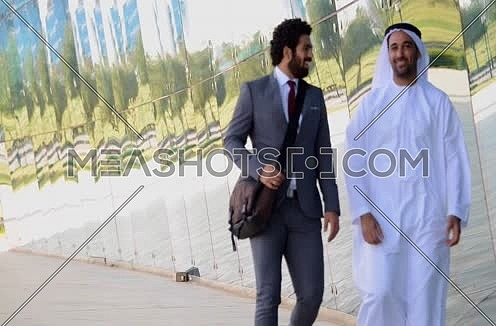 Two business men one wearing traditional emirati thob walking discussing
