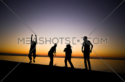 Four friends standing and jumping and having fun at the beach enjoying the golden hour by sunset golden hour