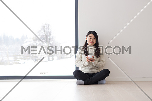 young beautiful asian woman enjoying morning coffee on the floor near window at cold winter day