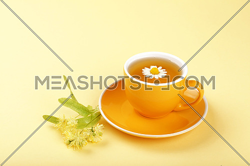 Close up one full yellow cup of herbal tea with camomile flower and linden on saucer over pastel paper background, high angle view
