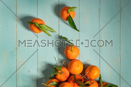 Fresh tangerines on blue wooden table. Copy space