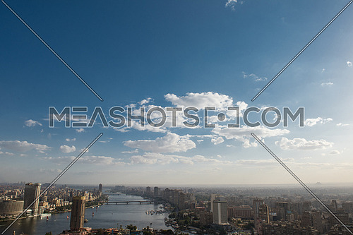 aerial view of modern Greater Cairo city downtown with Nile and pyramids in the horizon on a beautiful sunny day with blue sky and clouds capital of Egypt