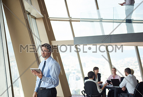 handosme business man working on tablet computer at modern bright office indoors with his team in group working together in background