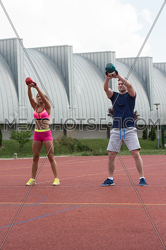 A Group Of Young People In Aerobics Class Doing A Kettle Bell Exercise Outdoor