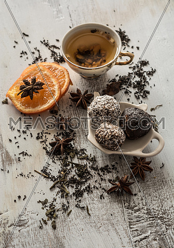 Tea, dried cinnamon, vegan cookies ,orange and anise on wooden b