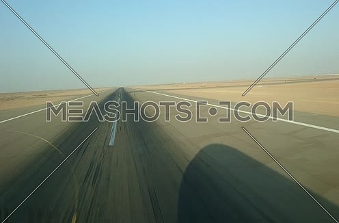 shot from plane window showing wing and runway while the plane is taking off