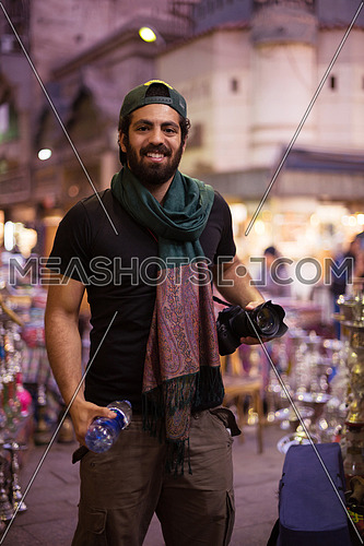 Portrait of a young middle eastern tourist with a camera in the traditional old town