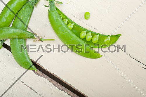 hearthy fresh green peas  over a rustic wood table
