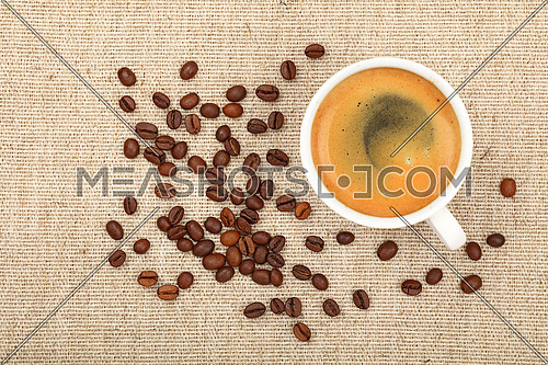 One full white cup of espresso or americano and roasted coffee beans on background of linen canvas