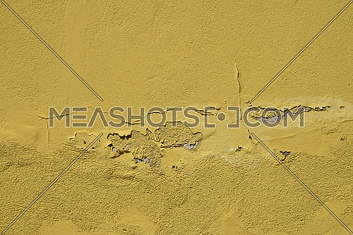 Vintage flakes of old faded yellow paint over abandoned grey concrete wall