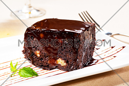 fresh baked delicious chocolate and walnuts cake with mint leaf beside
