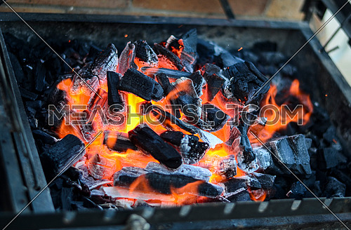 Coal and fire in a metal grill