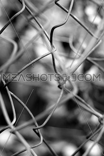 a wire fence blurred with an out of focus subject in the background