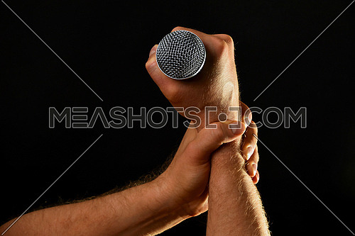 Two male hands holding microphone with wire cable isolated on black background