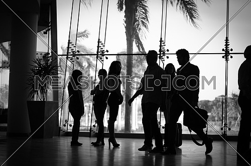 a silhouette view of businesswomen and two other men crossing the room