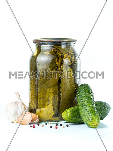 Pickled cucumbers isolated. Pickles in glass jar with garlic and peppercorn isolated on white background. Salted cucumber in jar isolated