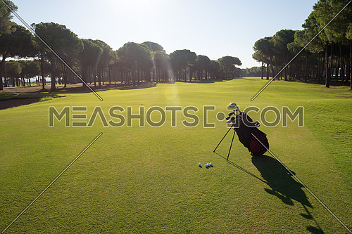 golf bag on course with  club and ball in front at beautiful sunrise