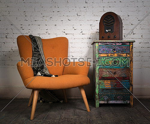 Composition of vintage orange armchair, colorful cupboard and aged wooden radio