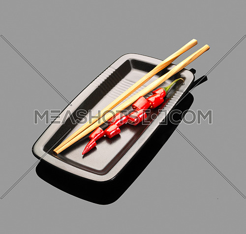 fresh red chili peppers on a plate with chopstikcs over grey reflective surface