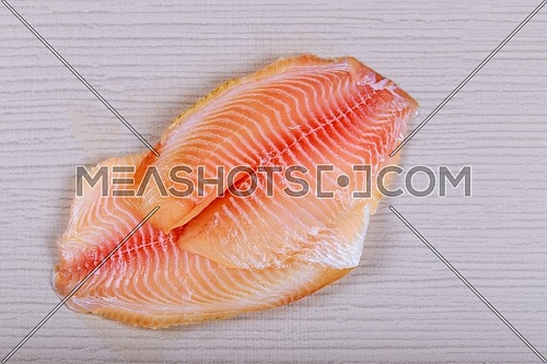 Raw fresh fish fillet tilapia with for cooking on table