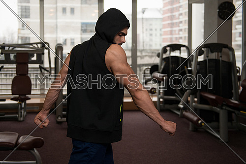 Young Muscular Man In Black Hooded Sweatshirt Showing Muscles