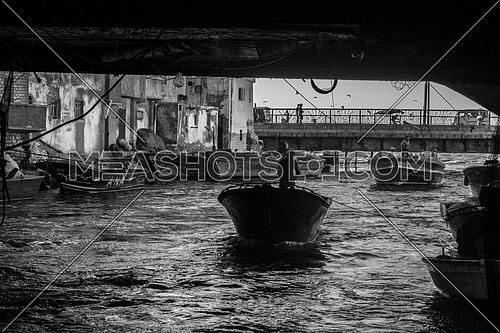 a black and white image of a man in a boat crossing under a bridge