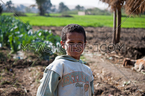 Farmer's son standing in the field working children concept