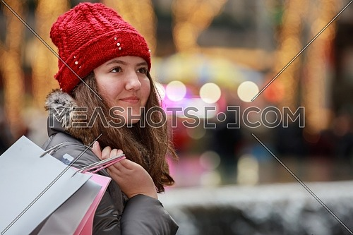 Beautiful young girl in holding shopping bags, smiling while walking down the street, colorful lights bokeh background