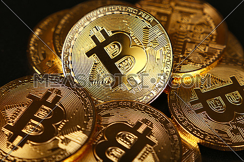 Close up heap of golden bitcoin physical coins over black background, high angle view, selective focus