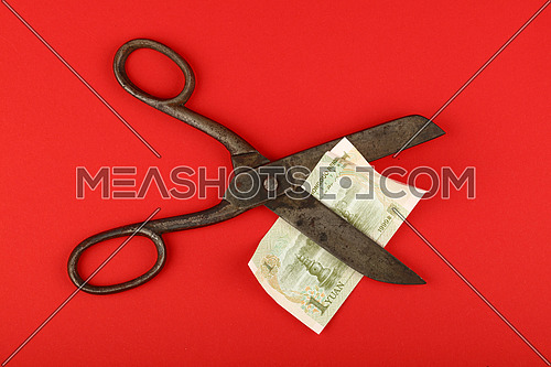China financial crisis, decline of Chinese economy and yuan exchange rate illustrated, old vintage scissors cut one yuan banknote on red background
