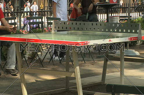 Medium shot for an adult male playing Ping pong in the park in new York City at day.