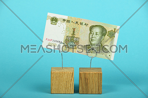 China economy crisis, decline of Chinese yuan illustrated, one yuan banknote at wooden metal holders over blue background