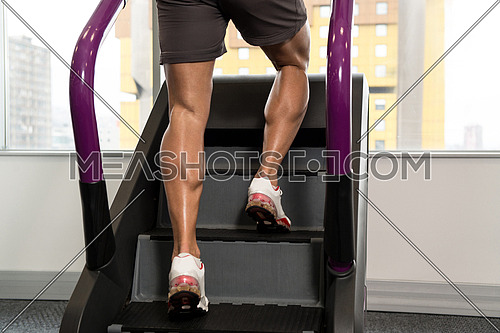 Close Up Of Male Legs Exercise On Stepper