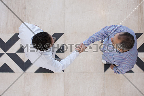 top view of smiling middle eastern doctor at the clinic giving an handshake to his patient, healthcare and professionalism concept