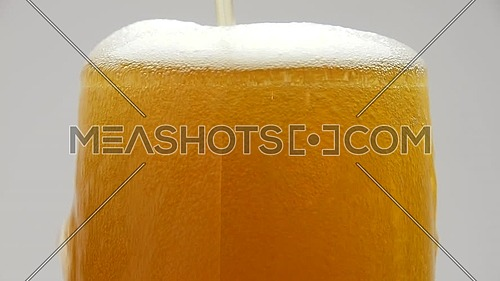 Close up background of pouring beer with bubbles and foam in glass, overfill and run out, flowing over the top, low angle side view, slow motion