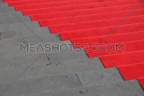 Close up red carpet over grey concrete stairs perspective ascending, high angle view