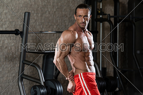 Mature Man Standing In Modern Fitness Center And Flexing Muscles