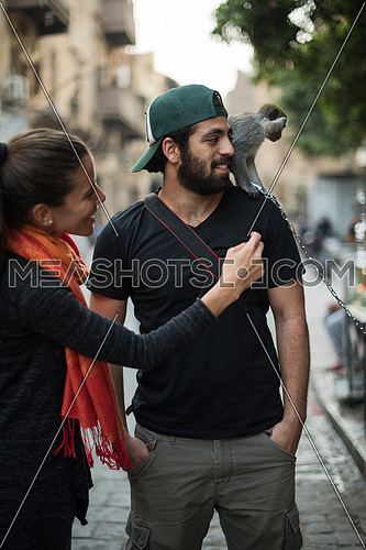 two young middle eastern tourists enjoy playing with a monkey in the city