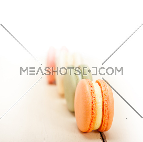colorful french macaroons over a white rustic wood table