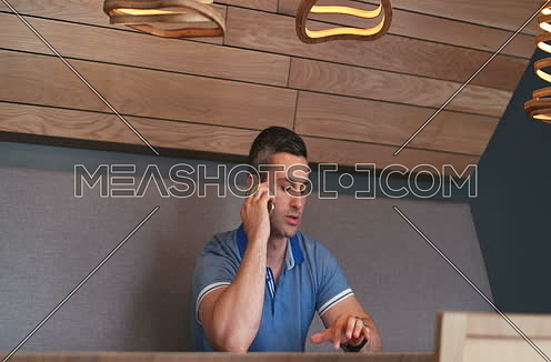 pan right for young man sitting in work space and talk on cell phone.