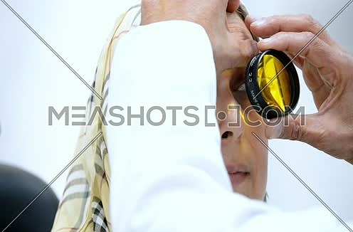 middle eastern senior ophthalmologist checking patient eyes