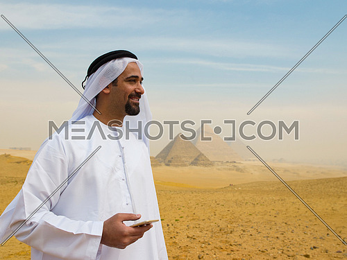 young man as tourist  wearing  arabian traditional clothes in egypt with giza pyramids in background  using smartphone